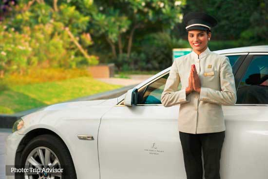 airport car service female chauffeur standing infront of vehicle